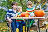 Dad And Two Little Sons Making Jack-o-lantern For Halloween In Autumn Garden