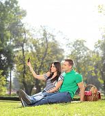 Girl taking a selfie with her boyfriend in a park shot with tilt and shift lens
