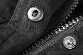 Zipper and button on clothes close up