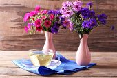 Still life of beautiful flowers in vase on wooden background