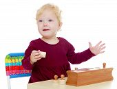 Charming little girl playing at the table