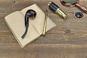 foto of spyglass  - Open Vintage Notebook With Blank Pages Gold Fountain Pen Retro Magnifier Compass and Spyglass On Grunge Woodeen Table Background - JPG
