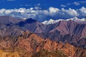 foto of jammu kashmir  - Rocky landscape with ice peaks and blue cloudy sky in background Ladakh Jammu and Kashmir India - JPG