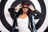 pic of cleavage  - Attractive young African woman in baseball cap adjusting her glasses while posing against black and white background - JPG
