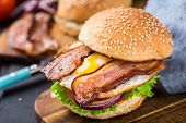 stock photo of burger  - Home made burger with bacon on wooden board - JPG