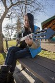 foto of sitting a bench  - An adult teen sits on a bench in a park and plays the guitar - JPG