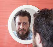 foto of beard  - Bearded man preparing to cut his beard with scissors - JPG
