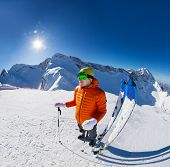 pic of caucus  - Guy standing with ski near in snow during sunny winter day on Krasnaya polyana ski resort with Caucasus mountains in Sochi - JPG