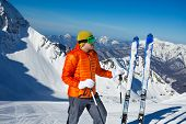 image of caucus  - Young man stands with ski in snow and beautiful mountain view on background in sunny weather on Krasnaya polyana - JPG