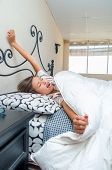 pic of yawn  - cute sleepy young girl waking up yawning in bed - JPG
