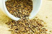 image of flax seed oil  - Flax seeds on a white cup and on top of burlap surface - JPG