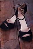 picture of tango  - Pair of black fabric tango shoes on worn out wooden floor - JPG