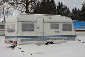 pic of camper  - camper covered by  snow in winter on a cloudy day - JPG