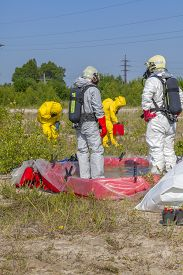 pic of hazardous  - Hazmat team members have been wearing protective suits to protect them from hazardous materials - JPG