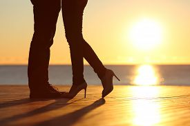 picture of hug  - Couple legs silhouette falling in love hugging at sunset on the beach with the sun in the background - JPG
