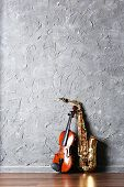 foto of saxophones  - Violin and saxophone on gray wall background - JPG