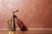 pic of saxophones  - Saxophone and violin on brown wall background - JPG