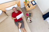 pic of bed breakfast  - High Angle View of Smiling Mature Man Lying on Bed with Laptop in Hotel Room with Remnants of Breakfast Tray and Personal Effects on Floor - JPG