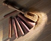image of cinnamon sticks  - cinnamon sticks and powder on a wooden table - JPG