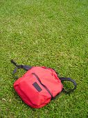 Single Red Bag Against Grass Field