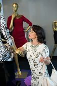 picture of dress mannequin  - Gorgeous Vietnamese woman looking at the dress on the mannequin - JPG