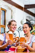 stock photo of pretzels  - Girlfriends with Pretzel and Beer in Bavarian Inn eating and drinking - JPG