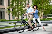 foto of opposites  - Young couple sitting on a bicycle opposite the green city park - JPG