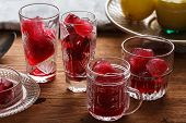 stock photo of sorrel  - Preparation of frozen hibiscus tea also known as karkade agua fresca or red sorrel on a wooden table - JPG