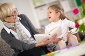 stock photo of grandma  - little girl with grandma reading interested book - JPG
