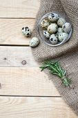 image of quail  - Quail eggs a bunch of rosemary and burlap are on the unpainted wooden background - JPG