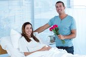 pic of hospital gown  - Handsome man offering bouquet of flowers to his pregnant wife in hospital room - JPG