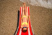 pic of sunbather  - Young and beautiful woman relaxing and having sunbath on the red sunbed in the sea - JPG