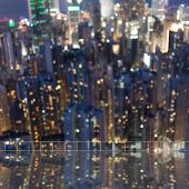 stock photo of skyscrapers  - Background of blurred skyscrapers at night with reflection on the roof of building in Hong Kong - JPG