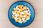 stock photo of curd  - Granular curd in blue glass plate mixed with peaches and raisins on wooden table top view - JPG