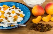 pic of curd  - Close up of curd with peaches and raisins bowl with sour cream on bamboo board - JPG