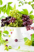 stock photo of cake stand  - Various types of grapes with leaves on a cake stand - JPG