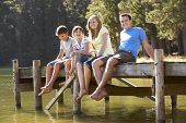 foto of jetties  - Family Sitting On Wooden Jetty Looking Out Over Lake - JPG
