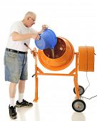 picture of mixer  - A senior adult man pouring sand into his cement mixer - JPG
