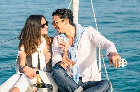 picture of champagne color  - Young couple in love on sail boat with champagne flute glasses  - JPG