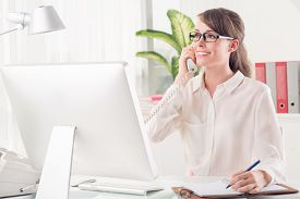 image of secretary  - Pretty secretary talking on telephone and making notes - JPG