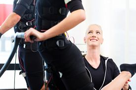 foto of stimulating  - Female coach giving man and woman ems electro muscular stimulation exercise  - JPG
