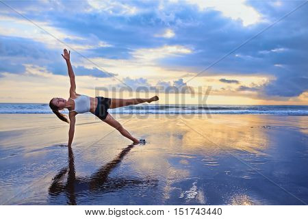 poster of Active sporty woman stand in yoga pose on black sand beach to keep fit and health. Sunset blue ocean surf background with sun. Woman fitness morning workout sport activity on summer family holiday