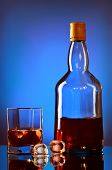 picture of boose  - whiskey bottle and glass on blue background - JPG