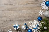 Christmas background with decorations and white gift boxes with blue ribbon on wooden table with cop poster