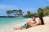Couple relaxing on suntan beach vacation relaxation holiday. Happy young adults sunbathing together  poster