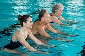 Happy smiling mature man and old woman cycling on a water bike in swimming pool. Happy and healthy s poster