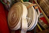 pic of firehose  - Antique Fire Hose rolled up on display in Fire Museum - JPG