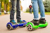 Feet Of Girl And Boy Riding Electric Mini Segway Outdoors In Park. poster