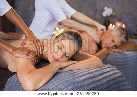 poster of Senior couple in spa salon getting massage. Relaxed senior couple enjoying body treatment in a welln