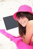 young woman on the beach with laptop
